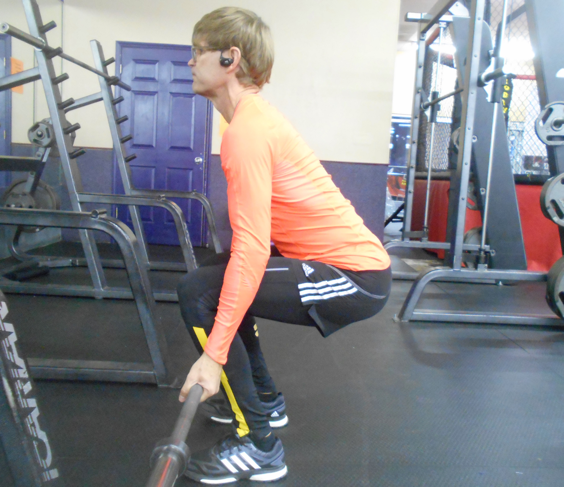 With inverted hand grips and neutral spine, drive hips forward during lift